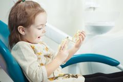 Child plays with artificial human jaw in dentist chair. Child plays with artificial human jaw with involved face expression in comfortable leather dentist chair royalty free stock photo