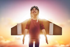 Child plays astronaut. Little child plays astronaut. Girl on the background of sunset sky. Kid in an astronaut costume plays and dreams of becoming a spaceman Royalty Free Stock Image