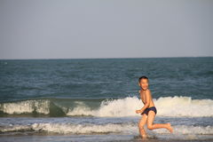 Child plays on the beach Stock Images