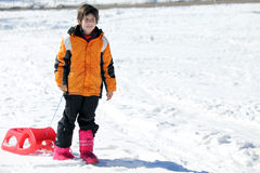 Child plays with bob in the snow Royalty Free Stock Image