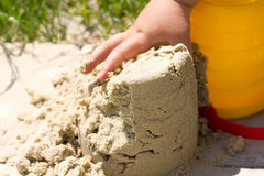 Child plays builds towers of sand Stock Photos
