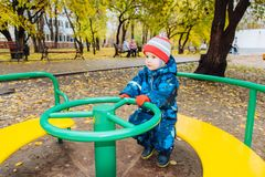The child is spinning on a swing in the playground in the park. The kid is spinning on a swing in the playground in the park stock photography