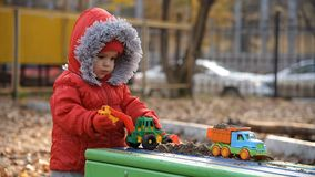 The child plays cars on the playground. The kid plays cars in the sandbox on the street stock video