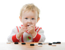 Child plays checkers on white. A little child plays checkers and gnaws it Royalty Free Stock Images