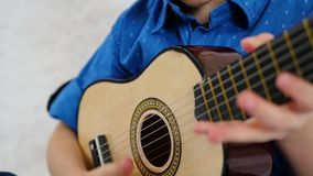 A child plays a children`s acoustic guitar in slow motion, close-up. The concept of education and child development. 4k stock video footage