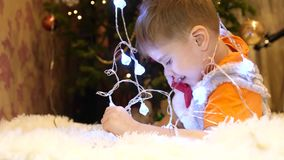 The child plays in the children`s room with a Christmas light, a garland . Happy childhood. The child plays in the children`s room with a Christmas light, a stock footage