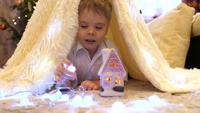 The child plays in the children`s room in a tent with a Christmas light. Happy childhood. The child plays in the children`s room in a tent with a Christmas light stock video