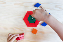 A child plays with colored blocks constructs a model on a light. Math, game, wooden blocks, children's hands, wood background, children's games Royalty Free Stock Image