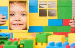 Child plays with construction bricks, looking through door of toy. Child plays with construction bricks on light background. Kid looking through door of toy royalty free stock images