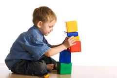 Child plays about cubes Royalty Free Stock Images