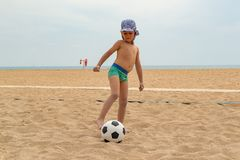 The child plays football on the beach stock images