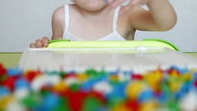 Child plays a game of developing motor skills, collect a designer multicolor mosaic for children, development of stock video