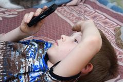 The child plays games on the mobile phone Stock Photo