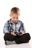 Child plays games on the mobile phone Stock Photos