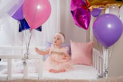 The child plays with the gift of a balloon while sitting in bed on your first birthday. Little beautiful girl in pink dress playing with balloon wand sitting in stock image
