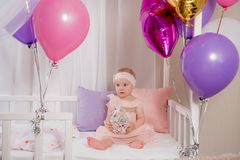 The child plays with the gift of a balloon while sitting in bed on your first birthday. A little girl sitting in a crib with a gift in his hands on his birthday royalty free stock photography