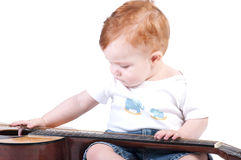 Child plays with a guitar Stock Image
