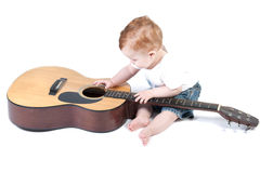 Child plays with a guitar Royalty Free Stock Image