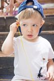 The child plays with headphones, listening to music from your phone. Royalty Free Stock Photo