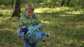 The child plays with his younger brother in the Park stock video