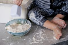 The child plays and indulges in flour on the kitchen table. Children`s feet are stained with white flour . Feet of the little coo royalty free stock photos