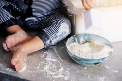 The child plays and indulges in flour on the kitchen table. Children`s feet are stained with white flour . Feet of the little coo royalty free stock photo