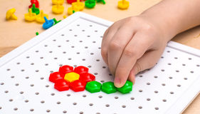 Child plays with a mosaic Stock Photo