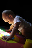 Child plays on the numeric puzzle mat Royalty Free Stock Photography