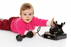 Child plays with an old phone. Lying klleines child plays with an old phone Royalty Free Stock Photo