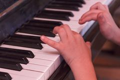 Child plays old piano with hands. Stock Photos