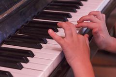 Child plays old piano with hands. Stock Photography