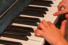 Child plays old piano with hands. Stock Image