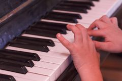 Child plays old piano with hands. Royalty Free Stock Image