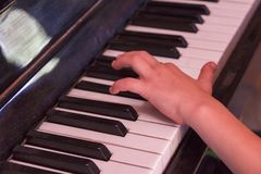 Child plays old piano with hands. Royalty Free Stock Photos