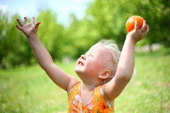 Child plays with orange. On the nature Royalty Free Stock Image