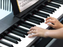 A child plays the piano Stock Photo