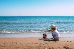 A child plays with a pink plastic bucket and shovel on the beach stock photography