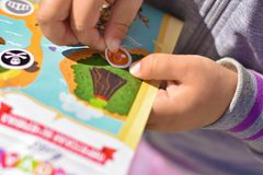 A child plays a pirate quest on a paper map, hands glue a sticker. Child plays a pirate quest on a paper map, hands glue a sticker stock photography