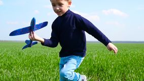 The child plays with the plane, experiencing emotions: happiness, joy, delight. The boy runs on the green grass stock video footage