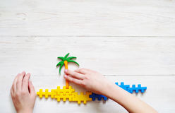 Child plays with the plastic blocs. Image of a palm tree and sea. Royalty Free Stock Image