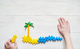 Child plays with the plastic blocs. Image of a palm tree and sea. Royalty Free Stock Photography