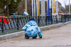The child plays on the playground one, a view from a back royalty free stock images