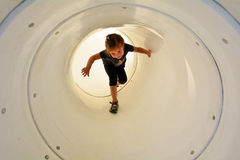 Child plays in playground tunnel Royalty Free Stock Image