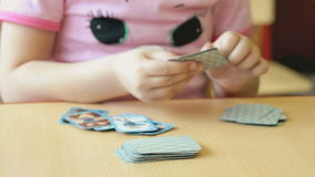 The child plays the playing cards at the table stock footage