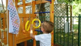 The child plays with pleasure in the playground with rings at a slow pace. Slow motion stock footage