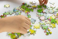 Child plays puzzles, children`s hand with colored toy puzzles stock image