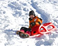 Child plays with red sled in the snow Royalty Free Stock Photos