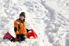 Child plays with red sled in the snow Royalty Free Stock Images