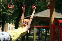 Child plays with rings of outdoor playground Stock Photography