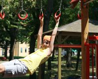 Child plays with rings of outdoor playground Stock Image